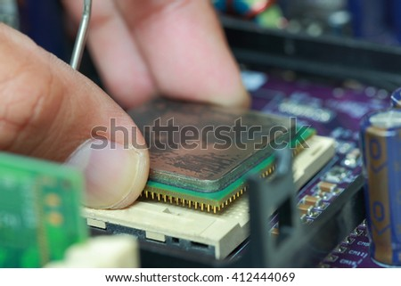Selective focus of finger hold CPU microprocessor and plug in CPU microprocessor to motherboard socket, mainboard computer. - stock photo
