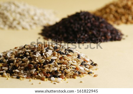Selective focus of four piles of mixed grains and seeds on a table. - stock photo