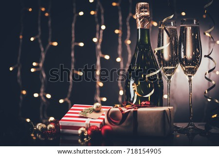 selective focus of glasses and bottle of champagne and presents against festive lights