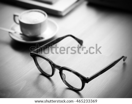 Selective focus of Glasses on Working Table with Coffee cup and book. Dramatic Light Black and white tone