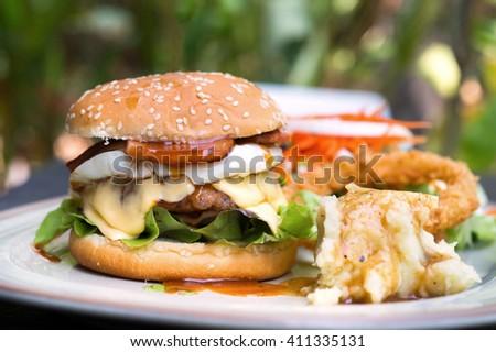 Selective focus of hamburger with ham and cheese, mash potato, deep fry onion ring and salad - stock photo