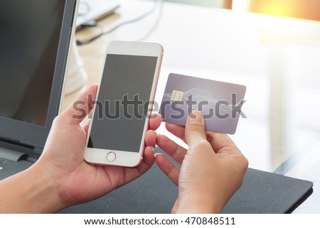 Selective focus of hands holding blank screen of white smartphone device and credit or debit card for buy or payment by phone.