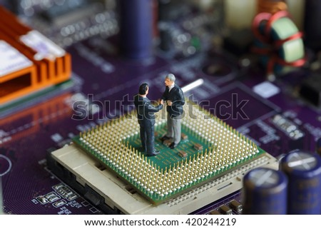 Selective focus of miniature businessman handshake on Control Processing Unit (CPU),  mainboard computer background as Commitment and Industry concept. - stock photo