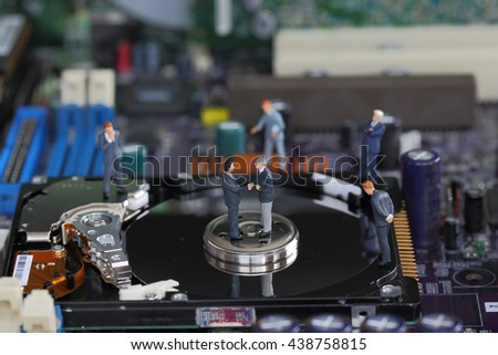 Selective focus of miniature businessman handshake on the disk of harddisk (hard disk) and fixed problem harddisk (hard disk) of Personal computer (PC) as business and industrial concept. - stock photo