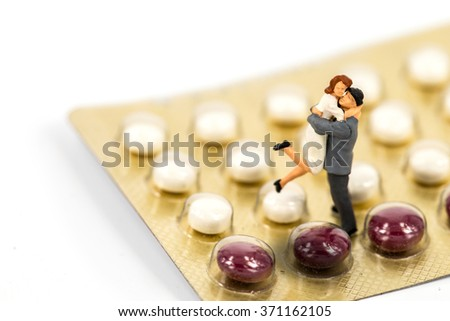 selective focus of miniature couple with birth control pills. abstract background to solution of birth control. - stock photo