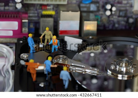 Selective focus of miniature engineer and worker and maintenance hard disk and fixed problem hard disk of Personal computer (PC) on blurred mainboard background as business and industrial concept. - stock photo