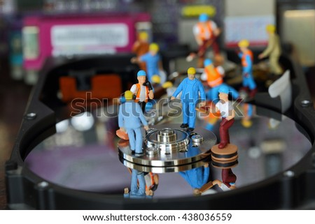 Selective focus of miniature engineer and worker discuss in job repair  harddisk (hard disk) and fixed problem harddisk (hard disk) of Personal computer (PC) as business and industrial concept. - stock photo