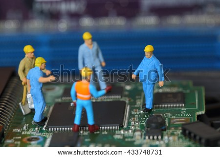 Selective focus of miniature engineer and worker fixed problem on chips and computer mainboard use for business and industrial background. - stock photo