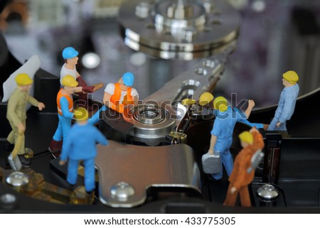 Selective focus of miniature engineer and worker maintenance hard disk or fixed problem hard disk of Personal computer (PC) as business and industrial concept. - stock photo