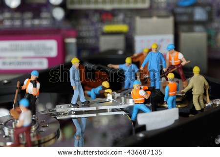 Selective focus of miniature engineer and worker maintenance harddisk (hard disk) and repair hard disk of Personal computer (PC) on blurred mainboard background as business and industrial concept. - stock photo