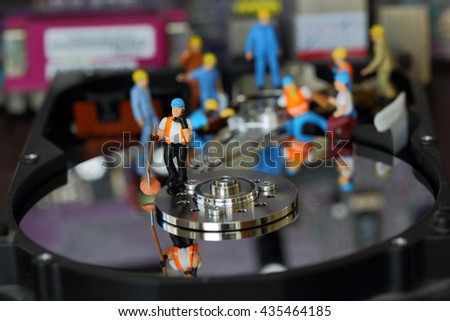 Selective focus of miniature engineer and worker use phone, mobile, smartphone, cellphone and fixed problem harddisk (hard disk) of Personal computer (PC) as technology and industrial concept. - stock photo
