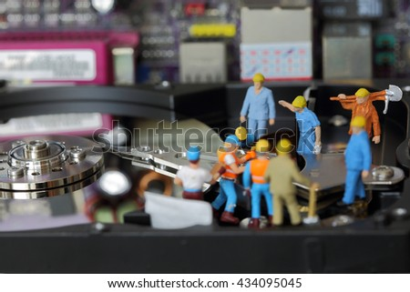Selective focus of miniature engineer and worker working and repair harddisk or  fixed problem harddisk (hard disk  of Personal computer (PC) as business and industrial concept. - stock photo