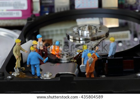 Selective focus of miniature engineer and worker working and repair harddisk or  fixed problem harddisk (hard disk)  of Personal computer (PC) as technology and industrial concept. - stock photo