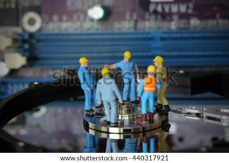 Selective focus of miniature engineer Headman meeting to fixed problem hard disk of Personal computer (PC) on blurred mainboard background as business and industrial concept. - stock photo