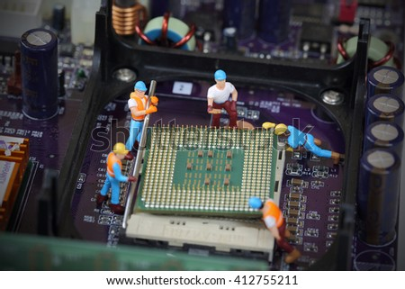 Selective focus of miniature engineer worker to fixed and repair CPU processor in mainboard computer and use for industry background. - stock photo
