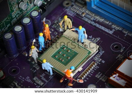 Selective focus of miniature engineer worker to fixed mainboard and repair Control Processing Unit (CPU) processor, mainboard computer and use for computer industry background or business background. - stock photo