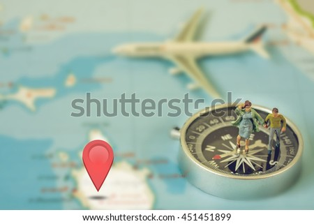 Selective Focus of Miniature people, Tourist Couple walking on Map with Plastic Toy Airplane, Compass over, and Sign to Destination Check in, Abstract Background to Travel Concept - stock photo
