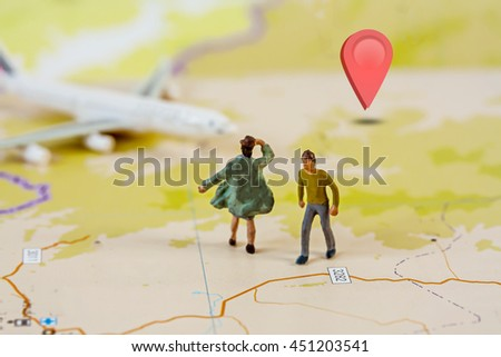 Selective Focus of Miniature, Tourist Couple people walking on Map with Plastic Toy Airplane and Sign to Destination Check in, Abstract Background to Travel Concept - stock photo