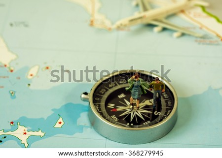 selective focus of miniature tourist on compass over map with plastic toy airplane,abstract background to travel concept - stock photo