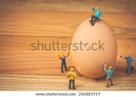 selective focus of miniature worker people sitting on egg , abstract background for idea  concept. - stock photo