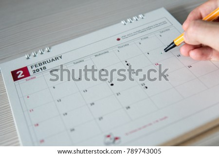 Selective focus of pen and hand pointing towards 9th February on paper calendar.