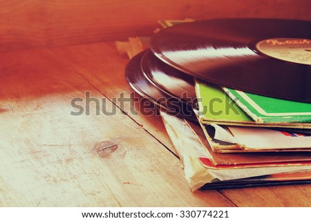 selective focus of records stack with record on top over wooden table. vintage filtered  - stock photo