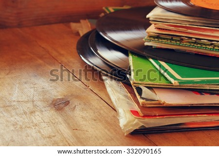 selective focus of selective focus image of records stack with record on top over wooden table. vintage filtered - stock photo