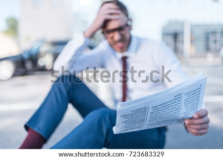 selective focus of stressed businessman with newspaper sitting on parking with car behind