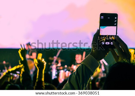selective focus of taking photo in concert  by smart phone - stock photo