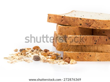 selective focus of the cereal and black sesame bread with whole grain cereal flakes which mixed warming cinnamon , red skin apple , golden raisins and roasted hazelnuts on white background - stock photo
