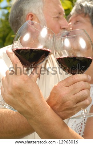 Selective focus of two seniors kissing while at a wine tasting