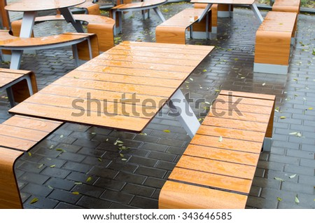Selective focus of wet outdoor cafe tables on the street after a rain fall on the wet pavement with a few yellow fallen leaves. - stock photo