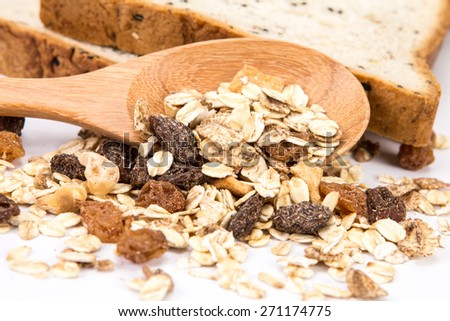 selective focus of whole grain cereal flakes which mixed warming cinnamon , red skin apple , golden raisins and roasted hazelnuts on white background - stock photo
