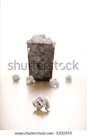 Selective focus of wire mesh trash can with crumpled paper scattered around. - stock photo