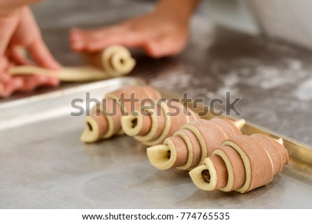 Selective focus on a row of double colored croissants with chocolate filling. Baker rolling puff pastry into rolls and bake it.