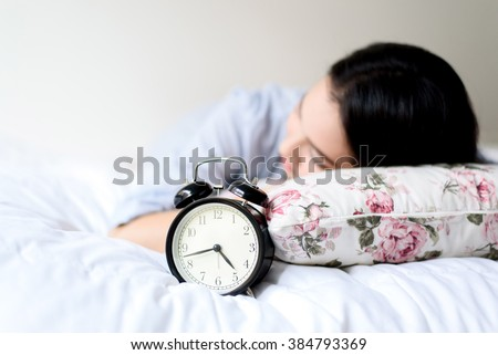 Selective focus on antique black alarm clock in front of young and beautiful asian girl on the bed.
