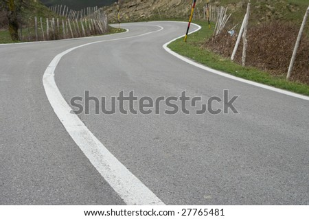 selective focus on asphalt of tortuous road - stock photo