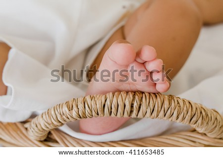 Selective focus on baby's feet, baby girl in a basket.  - stock photo