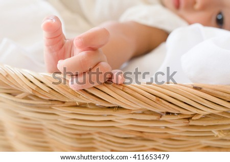 Selective focus on baby's hand, baby girl in a basket.  - stock photo