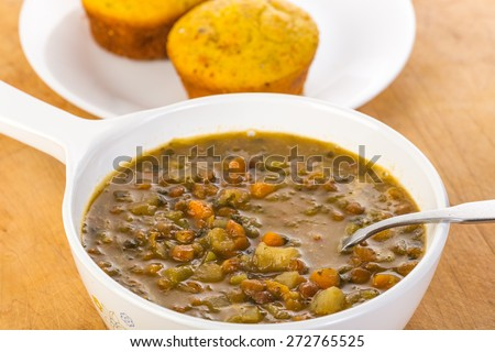 Selective focus on bowl of Organic Lentil with all organic ingredients.  Closeup with shallow depth of field.  Cornbread Muffin background. - stock photo
