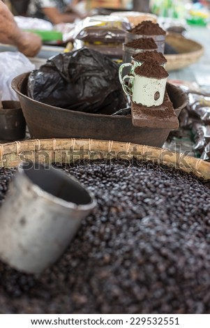 Selective focus on cups of ground roasted black coffee for sell in indonesian market (Sulawesi). - stock photo