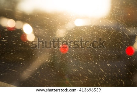 Selective focus on dusty windshield closeup and defocused cars as a whole background. - stock photo