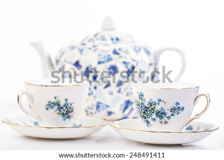 Selective focus on Elegant Fine China Tea Cups in blue floral pattern with tea pot  out of focus in background. - stock photo