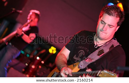 Selective focus on guitar player with bass player in background playing a rock show - stock photo