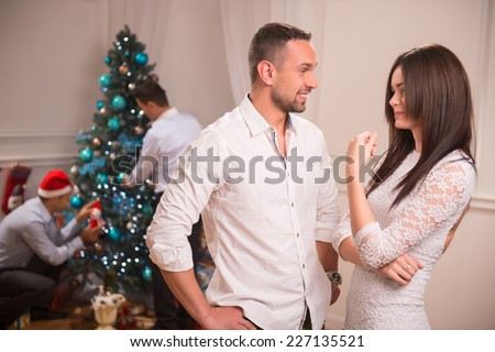 Selective focus on handsome guy wearing white shirt speaking with the beautiful dark-haired smiling girl wearing white dress about the great corporate party. Two men decorating the New Year tree on - stock photo