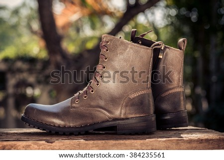 Selective focus on left boot and dark vintage tone color on the garden background