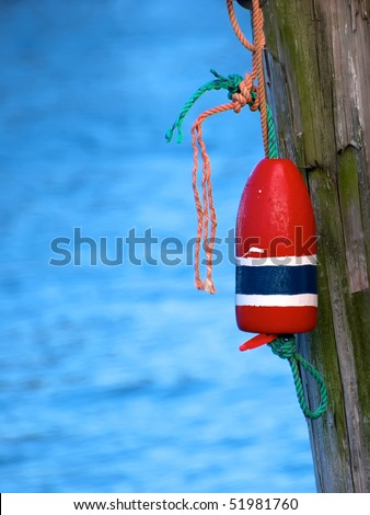 Selective focus on Lobster Buoy. Lobster Buoy tied with rope to a wood pier pylon.  Blue rough ocean water background - stock photo