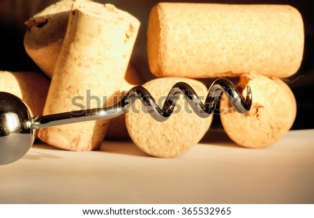 Selective focus on metal corkscrew and set of wine corks on rustic background.  - stock photo