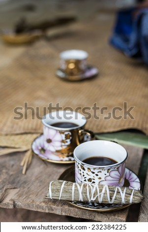 Selective focus on one of three cups of black coffee with traditional snack (sweet rice rolled inside palm leaf) on wooden bench. Sulawesi, Indonesia. - stock photo