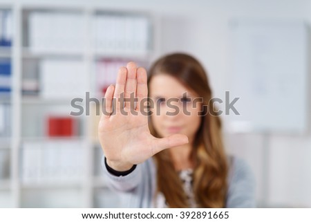 Selective focus on palm of woman in long brown hair facing front with whiteboard and bookshelf in background